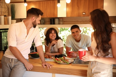 Happy young people having breakfast in trailer. Camping vacation