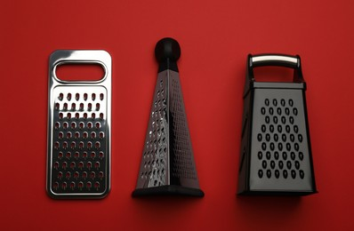 Different modern graters on red background, flat lay