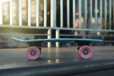 Modern light blue skateboard with pink wheels on top of ramp outdoors