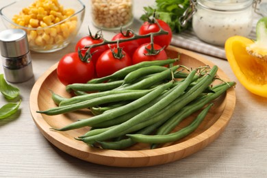 Fresh green beans and other ingredients for salad on white wooden table