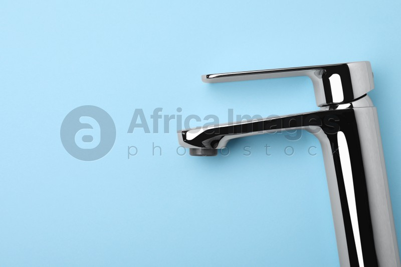 Single handle water tap on light blue background, top view. Space for text
