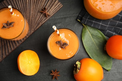 Tasty persimmon smoothie with anise and fresh fruits on black table, flat lay