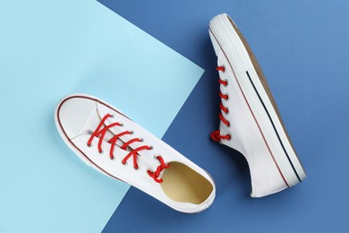 Pair of trendy sneakers on color background, flat lay