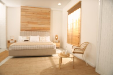 Blurred view of stylish hotel room interior with comfortable bed