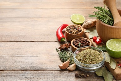 Different natural spices and herbs on wooden table, space for text