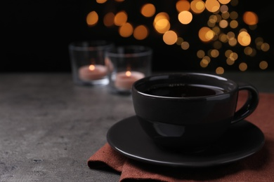 Cup of hot coffee on dark table against black background, space for text