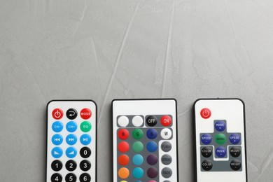 Remote controls on grey table, flat lay. Space for text