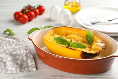 Half of cooked spaghetti squash with basil in baking dish on white wooden table
