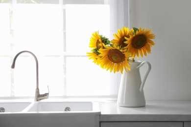 Bouquet of beautiful sunflowers on counter in kitchen
