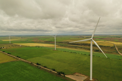 Aerial view of wind turbines in field on cloudy day