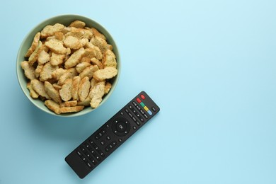 Remote control and rusks on light blue background, flat lay. Space for text