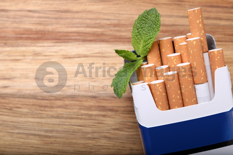 Pack of menthol cigarettes and mint leaves on wooden table, flat lay. Space for text