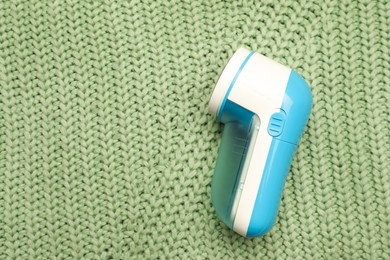 Modern fabric shaver for removing lint on green knitted cloth, top view