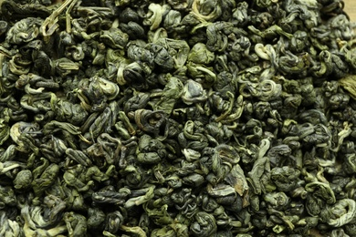 Dry green tea leaves as background, top view