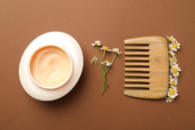 Jar of hair care cosmetic product, wooden comb and beautiful chamomile flowers on brown background, flat lay