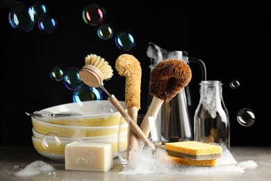 Cleaning supplies for dish washing and soap bubbles on black background