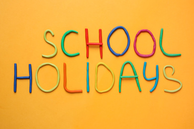 Text School Holidays made of modelling clay on orange background, flat lay