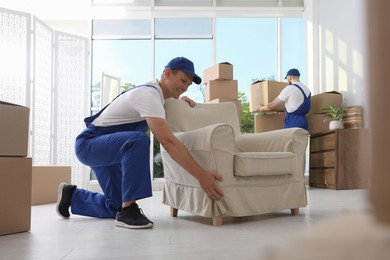 Moving service employees with armchair and cardboard boxes in room