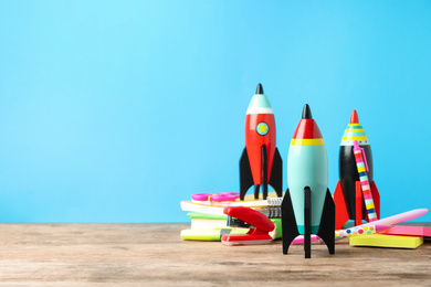 Bright toy rockets and school supplies on wooden table. Space for text