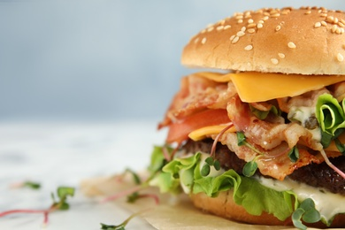 Tasty burger with bacon on table, closeup. Space for text