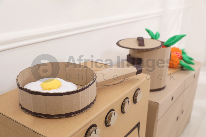 Toy cardboard kitchen with frying pan indoors