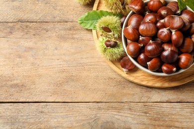 Fresh sweet edible chestnuts on wooden table, top view. Space for text