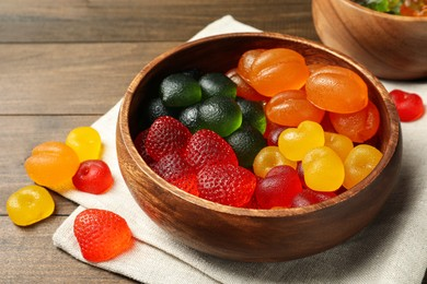 Delicious gummy candies in bowl on wooden table