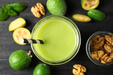 Fresh feijoa smoothie in glass on black wooden table, flat lay
