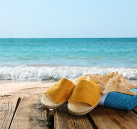 Beach accessories on wooden surface near ocean, space for text