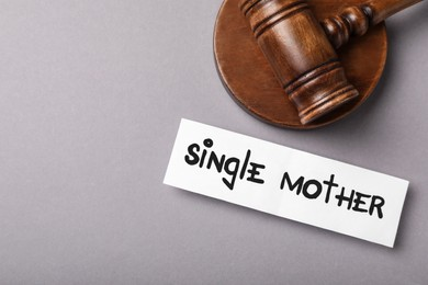Being single mother after divorce concept. Card and judge gavel on grey background, flat lay