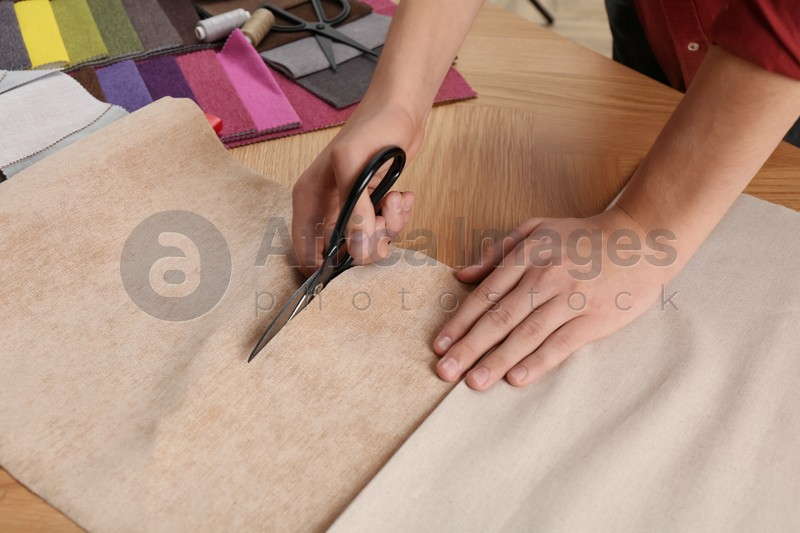 Man cutting beige fabric with scissors at wooden table, closeup