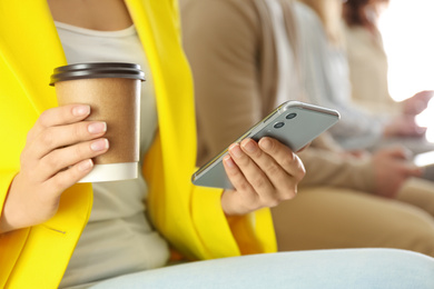 Woman with cup of coffee using smartphone, closeup
