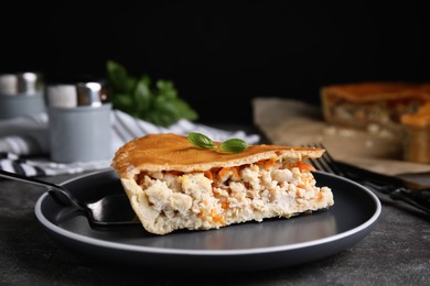 Piece of delicious pie with meat and basil on grey table