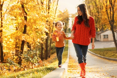 Happy woman with daughter walking in sunny autumn park