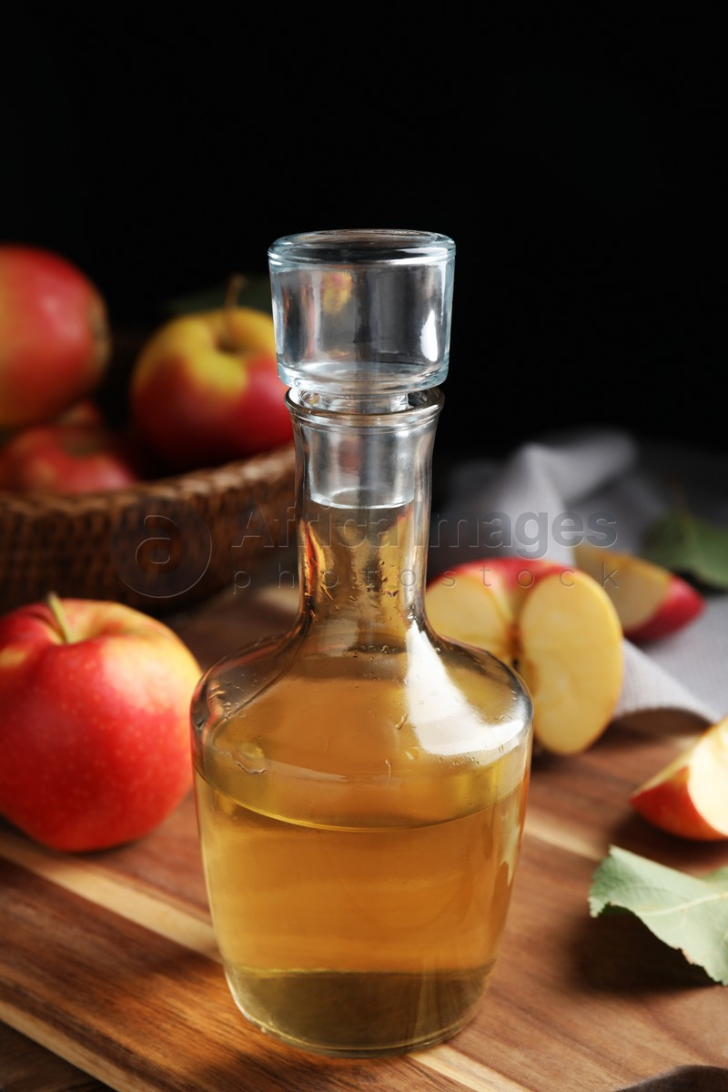 Natural apple vinegar and fresh fruits on wooden table