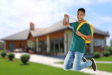 Happy African American teenage boy jumping near house, space for text . School holidays
