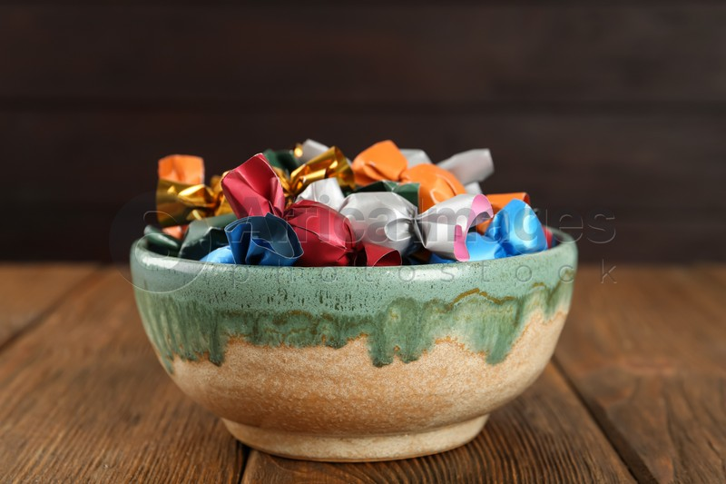 Candies in colorful wrappers on wooden table, closeup
