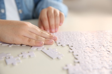 Little girl playing with puzzles at table, closeup