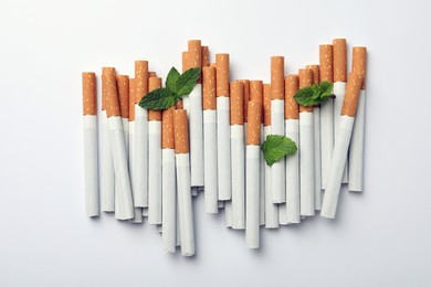 Menthol cigarettes and fresh mint leaves on white background, flat lay