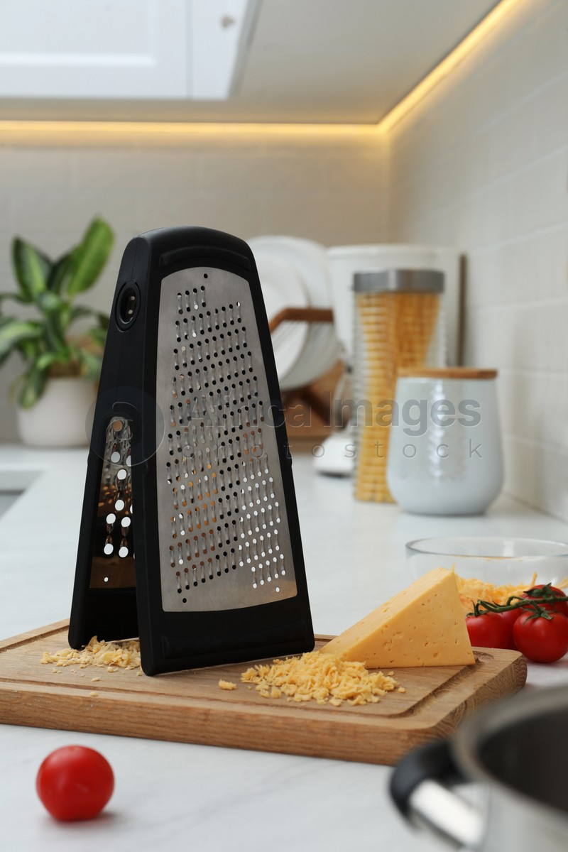 Grater, cheese and cherry tomatoes on kitchen counter