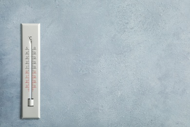 Weather thermometer on grey wall. Space for text