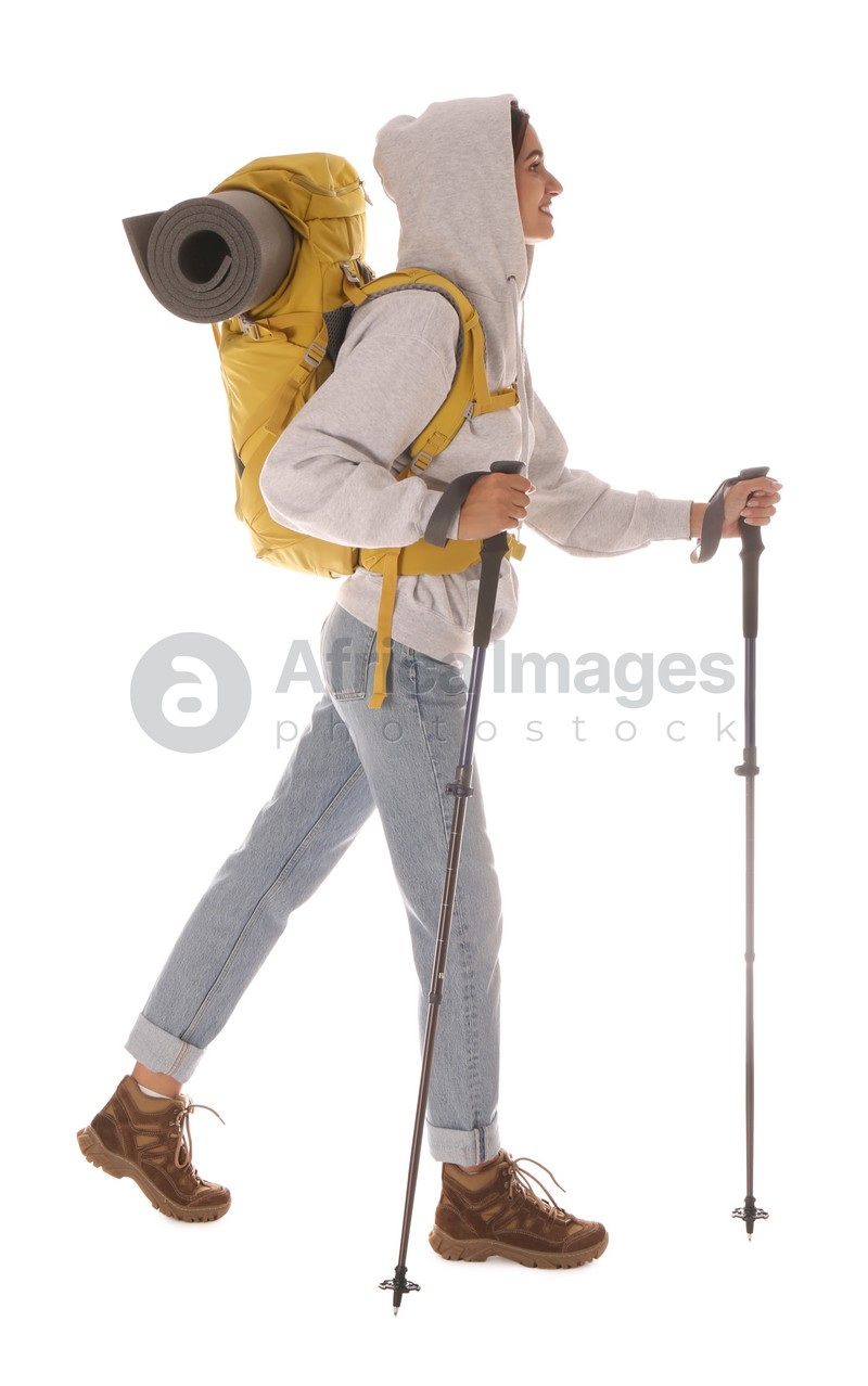 Female hiker with backpack and trekking poles on white background