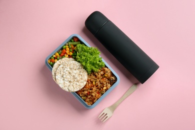 Thermos and lunch box with food on pink background, flat lay