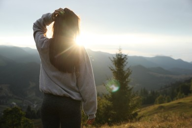 Beautiful young woman enjoying her time in mountains, back view. Space for text