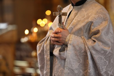 Priest holding cross in church, closeup. Baptism ceremony