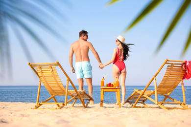 Happy couple resting on sunny beach at resort