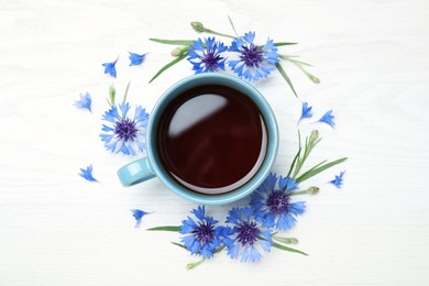 Cup of tea and cornflowers on white wooden table, flat lay