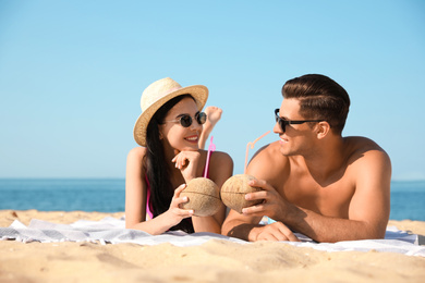 Happy couple with cocktails on sunny beach at resort