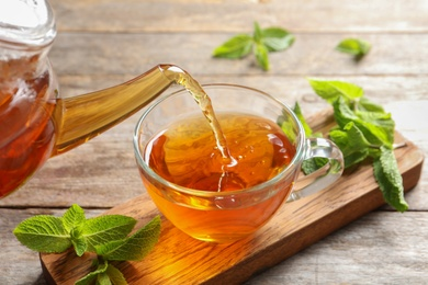 Pouring hot aromatic mint tea into cup on wooden board