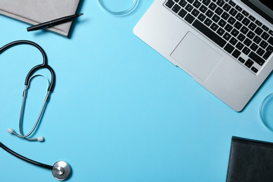 Modern laptop and medical students stuff on color background, top view. Space for text